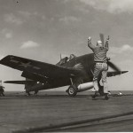 Deck crew guide a Hellcat to takeoff. Gift In Memory of John Valdemor Peterson, 2011.228