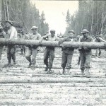 """A heavy log for a corduroy road bed at the J-35 mile mark is carried by seven husky Company C men. After a job like this, chow and sleep were always welcome."""