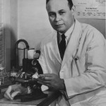 Dr. Charles Drew in lab with microscope, ca.1940-1941.  Photo, Scurlock Studio Records.