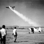 In an early test, a rocket-assisted airplane takes off faster and using a shorter runway than a propeller driven aircraft (still on the ground).  Photo, JPL.