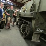 Normandy Academy students observe a Halftrack up close in the Museum's warehouse