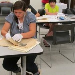 Sara Allen examines documents related to the 82nd Airborne Division during World War II.