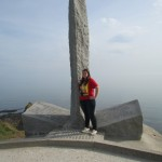 Sara Allen from Utah stands near the monument to the US Army Rangers at Pointe du Hoc.