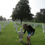 A Normandy Academy student lays a rose at the grave of a fallen American soldier.