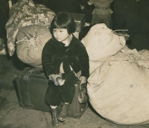 A young Japanese American evacuee waits with the family's luggage before leaving for an assemby center, 1942. Courtesy of the National Archives.