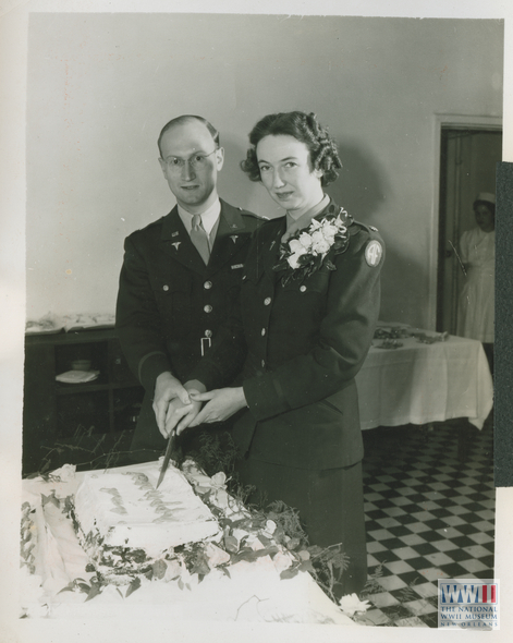 Newlyweds Lt. Col. Stewart F. Alexander, medical consultant in chemical warfare, and Lt. Col. Bernice Wilbur, Director of American Nurses in the North African theater, cutting their wedding cake after their marriage.  Algiers, Algeria. 29 April. 1994.  U.S. Army Signal Corps photograph, from the collection of The National WWII Museum.