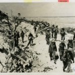 Marines on the march on a Kwajalein beach in 1944. US Navy Official photograph, Gift of Charles Ives, from the collection of The National WWII Museum.