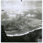 Aerial view of Kwajalein shows landing craft approaching in 1944. US Navy Official photograph, Gift of Charles Ives, from the collection of The National WWII Museum.