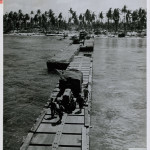 A floating highway of pontoon sections leads from an LST to the shores of Kwajalein Atoll in the Marshalls on January 31 – February 2, 1944. US Navy Official photograph, Gift of Charles Ives, from the collection of The National WWII Museum.