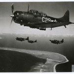 A formation of Douglas Dauntless dive-bombers wheel around for their run on the target far below, Eniwetok on February 18, 1944. U.S. Navy Official photograph, Gift of Charles Ives, from the collection of The National WWII Museum.