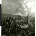 Mt. Vesuvius belches huge clouds of smoke and volcanic ash over the remains of San Sebastiano, Italy, partially destroyed by the lave stream from the erupting volcano, March 24, 1944. U.S. Army Signal Corps photograph from the collection of The National WWII Museum.