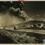 Vesuvius erupting with vehicles on a road in foreground. A large fleet of Army vehicles were used to evacuate the villagers who lived in the path of Vesuvius' lava. U.S. Navy Official photograph, Gift of Charles Ives, from the collection of The National WWII Museum.