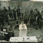 "Original caption: Signal Corps radio telephoto. Italy. ""German troops included in American Easter services (via loud speaker)! Hostilities ceased for one hour on this front-line sector during services, conducted by American troops and directed across the lines by specifically installed amplifiers. Here, Chaplain Leo J. Crowley says Mass to a group of soldiers who were close enough to leave their foxholes to attend."" Italy. 9 April 1944"