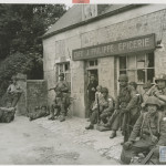 """Exhausted from their rapid advance inland from the Normandy beachhead, U.S. soldiers relax for a few minutes outside of a French cafe."" 20 June 1944. U.S. Navy Official photograph, Gift of Charles Ives, from the collection of the National WWII Museum. 2011.102.386"