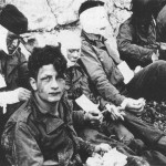 Wounded men on Omaha Beach. Army Signal Corps Collection, The National Archives and Records Administration.