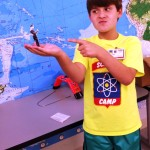 Campers create optical illusions using WWII-themed cut outs.