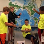 Using flexible tubing and marbles, campers experiment with the physics of roller coasters.