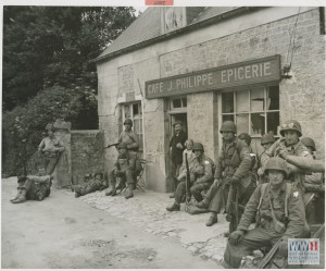 Exhausted from their rapid advance inland from the Normandy beachhead, U.S. soldiers relax for a few minutes in Normandy, France in June 1944.  U.S. Army Signal Corps photograph, Gift of Regan Forrester, from the collection of The National WWII Museum. 2002.337.938