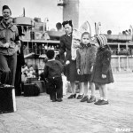 Aleutian American woman and children prepare to leave Dutch Harbor, Alaska for internment camps in 1942. Courtesy of the National Archives and Records Administration.