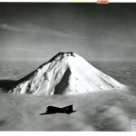 """Outlined Against the Cloudy Cloak of Snow-Capped Gareloi Volcano, a Naval Air Transport Flies through the Aleutians Towards Bleak Attu, October 1943."" U.S. Navy Official photograph, Gift of Charles Ives, from the collection of The National WWII Museum. 2011.102.347."