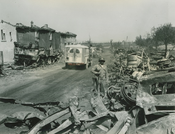 Soldier stands alongside the rubble of the town of Loriol-sur-Drome, France on September 3, 1944. U.S. Army Signal Corps photograph, Gift of Regan Forrester, from the collection of The National WWII Museum. 2002.337.896