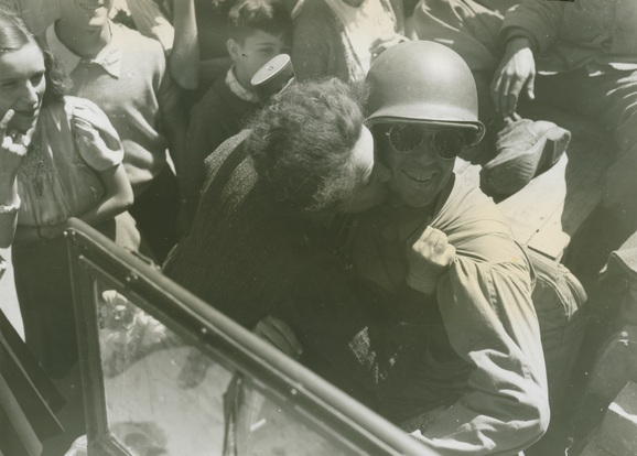 Elderly French lady gratefully kisses a US soldier in Bourg, (likely Rhône-Alpes), France on September 6, 1944.  U.S. Army Signal Corps photograph, Gift of Regan Forrester, from the collection of The National WWII Museum. 2002.337.907