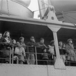 Aboard the USS Delarof, residents of St. Paul, Alaska gaze back at their homes en route to internment camps in Southeast Alaska. 1942. Courtesy of the National Archives and Records Administration.