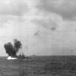 Japanese aerial torpedo hits the ship's starboard quarter, during the afternoon of 16 October 1944. This view shows burning fuel at the base of the torpedo explosion's water column. Houston had been torpedoed amidships on 14 October, while off Formosa, and was under tow by USS Pawnee (ATF 74) when enemy torpedo planes hit her again. USS Canberra (CA 70), also torpedoed off Formosa, is under tow in the distance.   Official U.S. Navy Photograph, from the collections of the Naval Historical Center #NH 98826.