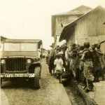 A group of local children gather near a US Army jeep in Ghana in the 1940s. Gift of Jason Sloan, from the collection of The National WWII Museum.