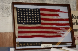 PT-305's original flags. In the frame, the battle flag is pictured above while the commissioning flag lies below it.
