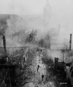 Infantrymen of the 255th Infantry Regiment move down a street in Waldenburg to hunt out the Hun after a recent raid by 63rd Division. Image courtesy of National Archives.