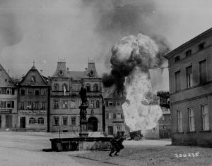 Two anti-tank Infantrymen of the 101st Infantry Regiment, dash past a blazing German gasoline trailer in square of Kronach, Germany. Courtesy of National Archives.