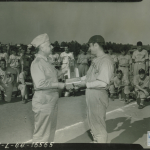 Sgt Rammazotti of the 5th Inf baseball team receiving trophy from Maj Gen Landrum, 71st Div Commander with 5th Inf and 66th Inf teams in background at Tiger Field, Sand Hill area, Fort Benning, Georgia.