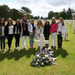 French educator Christelle Zuccolotto and her students at Frank Bradetich's gravesite, Normandy, France.