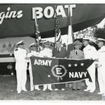 """New Orleans shipbuilder Andrew Higgins receives the """"E"""" for Excellence pennant for production after he produces the 10,000 Higgins Boat, July 1944. Gift in memory of Andres N. Horcasitas, from the collection of The National WWII Museum, 2009.428.010."""