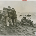 Wounded Marines on Iwo Jima are being taken to an aid station.  U.S. Navy, Gift of Charles Ives, from the collection of The National WWII Museum. 2011.102.538.