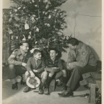An American and a British soldier with two Italian boys under a Christmas tree on Christmas day 1944 near Scarperia, Italy