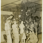 U.S. servicemen and Red Cross women decorating a Christmas tree at the Times Square Club, an American Red Cross club on Tinian