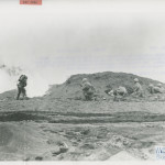 SOLDIER WITH FLAME-THROWER IS SUPPORTED BY MARINE RIFLEMEN ON IWO JIMA IN FEBRUARY 1945. U.S. Navy Official photograph, Gift of Charles Ives, from the collection of The National World War II Museum.