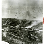 U. S. NAVY CARRIER-BASED GRUMMAN FIGHTER PLANES SWOOP DOWN TO ATTACK JAPANESE INSTALLATION ON IWO JIMA ON 21 FEBRUARY 1945. U.S. Navy Official photograph, Gift of Charles Ives, from the collection of The National World War II Museum.