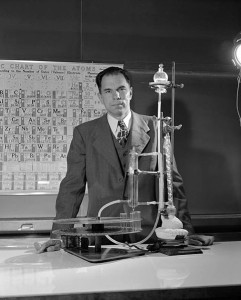 A young Glenn Seaborg posing in front of a Periodic Table showing gaps which would eventually be filled with elements he would help discover.