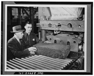 A block of synthetic rubber comes off the line, and is headed for the baler. From the Library of Congress.