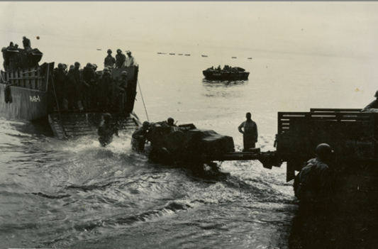 A CCKW truck tows an artillery piece onto a shore during amphibious training on Guadalcanal in March 1944