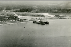 Two LSTs on a beach on Guadalcanal with Henderson Field Runways in 1943.