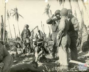 7th Infantry division soldiers helping local population for eventual evacuation off island on Kwajalein in February 1944