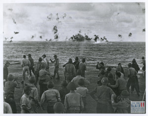 Pilots and crewman aboard a U.S. Navy carrier cheer as guns strike a smashing blow to a Japanese plane in the Marianas on 22 February 1944