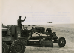 A Seabee in a road grader waves as a Boeing B-29 Superfortress prepares to land on Tinian in March 1945