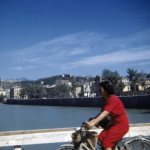 A civilian woman rides her bicycle across a bridge in Verona, Italy in 1944 or 1945