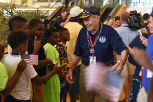 WWII Veteran being greeted by a youth baseball team upon arrival to New Orleans.