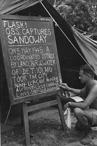 Pfc. Edeleanu prints news bulletin on bulletin board outside Intelligence tent of Kyaukpyu Camo the day before OSS, AFU, and departure via convoy for Rangoon.